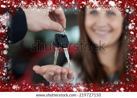 Composite image of woman smiling while receiving car keys against snow - stock photo