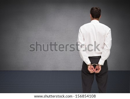 Composite image of young businessman wearing handcuffs in grey room - stock photo