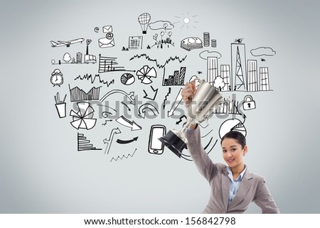 Composite image of young businesswoman showing a cup in front of economic illustrations - stock photo