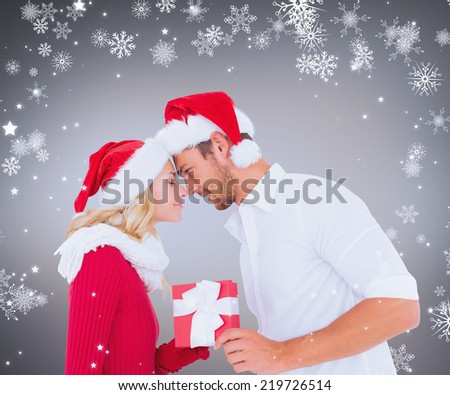 Composite image of young festive couple against grey vignette - stock photo