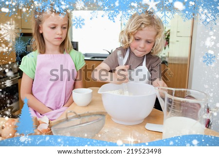 Composite image of young siblings preparing dough against snow - stock photo