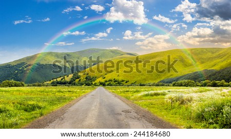 composite landscape with abandoned asphalt road rolls through meadows with flowers going to high  mountains in morning light with rainbow - stock photo