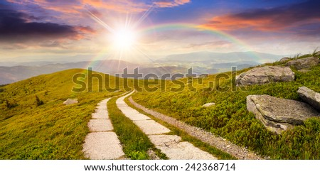 composite panorama Landscape with road on a hillside with huge stones and conifer trees  near mountain peak in sunset light with rainbow - stock photo