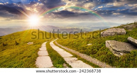 composite panorama Landscape with road on a hillside with huge stones and conifer trees  near mountain peak in sunset light with rainbow