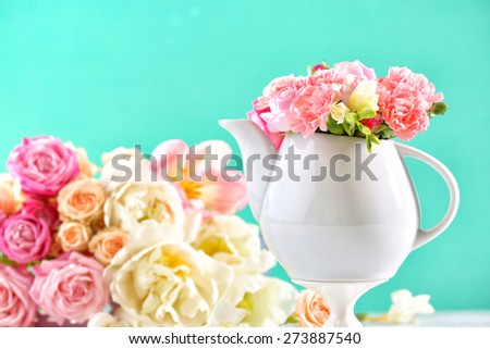 Composition beautiful spring flowers in teapot on light blue background - stock photo