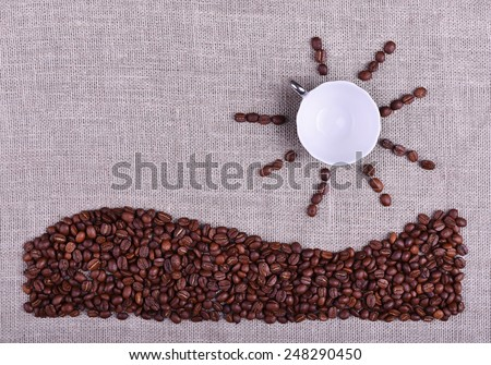 Composition cup of coffee with sun and sea made by coffee beans on linen texture table - stock photo