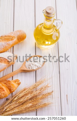 composition ears of rye croissant baguettes flour in spoon bottle oil on white boards food and drink concept  - stock photo