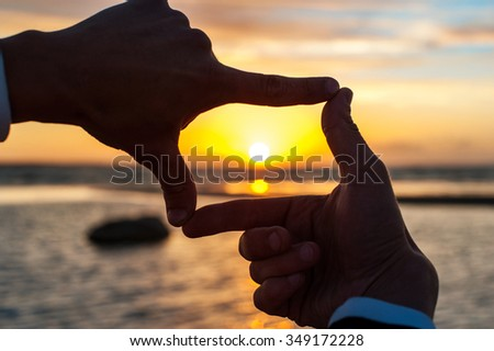 Composition finger frame- man's hands capture the sunset. Multicolored horizontal outdoors image. - stock photo
