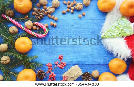 Composition for Christmas and New year - oranges, walnuts, hazelnuts, candies, meringue, cookies, cranberry, clove, cinnamon and star anise. Spices, sweets and nuts. Christmas background