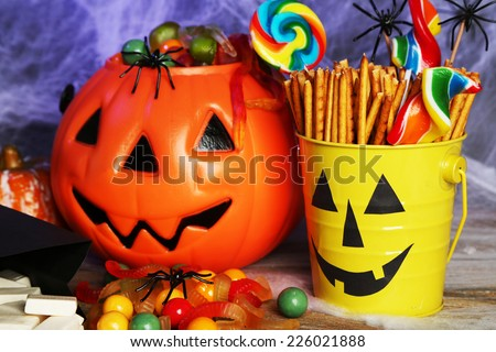Composition for Halloween with sweets on wooden table