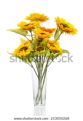 Composition from bright artificial sunflowers in glass vase isolated on white background. Closeup. - stock photo