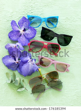 composition from sunglasses in different colors against a green wall including flowers - stock photo