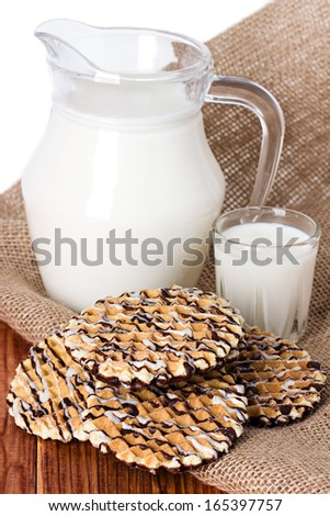 Composition milk in a jug, a glass on burlap background