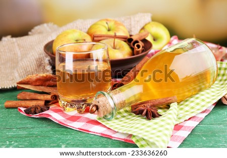 Composition of apple cider with cinnamon sticks, fresh apples on wooden table, on bright background - stock photo