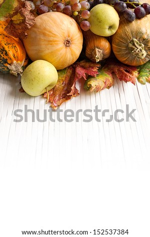 Composition of autumn pumpkins with apple and grapes on the wooden background - stock photo