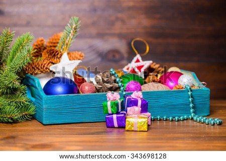composition of branch fir tree, vintage wooden box with Christmas decoration, pinecones, stars, balls and gifts on wooden background, closeup - stock photo