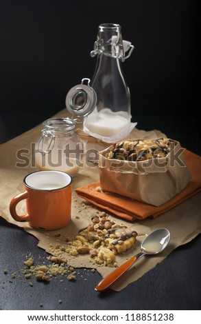 Composition of broken peanut cookies with chocolate and a mug of milk, with a bottle of milk and a jar of condensed milk, shot in dark tones. - stock photo