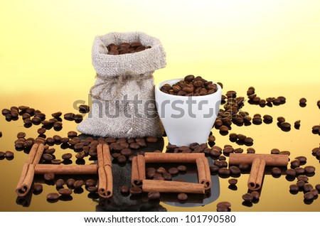Composition of canvas sack and the cup with coffee beans on bright background. Hot.
