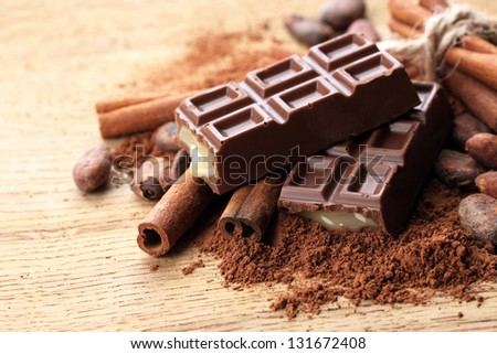 Composition of chocolate sweets, cocoa and  spices on wooden background - stock photo