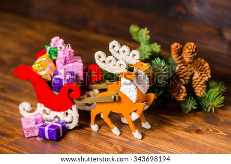 composition of Christmas decoration reindeer and Santa sleigh hand made with gifts, branch fir tree, pinecones on wooden background, closeup - stock photo