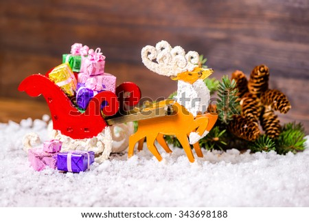 composition of Christmas decoration reindeer and Santa sleigh with gifts, branch fir tree, pinecones in snow on wooden background, closeup - stock photo