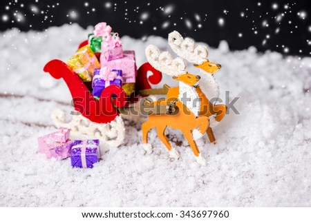 composition of Christmas decoration reindeer and Santa sleigh with gifts in traces snow on black background, closeup - stock photo