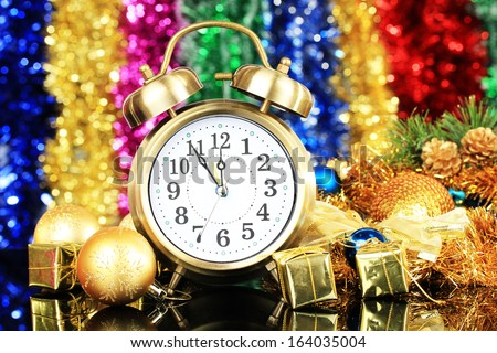 Composition of clock and christmas decorations on bright background - stock photo