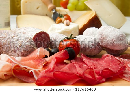 composition of cold cuts  on wooden board with different type of cheese - stock photo