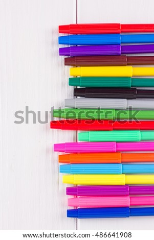 Composition of colored markers on a white background
