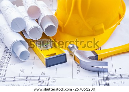 composition of construction tools hammer helmet level blueprints - stock photo