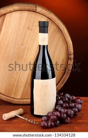 Composition of corkscrew and bottle of wine, grape, wooden barrel  on wooden table on dark background - stock photo