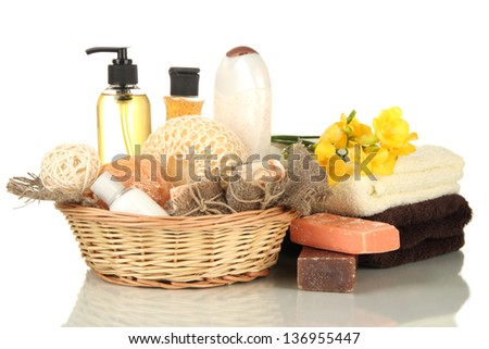 Composition of cosmetic bottles and soap in basket, isolated on white