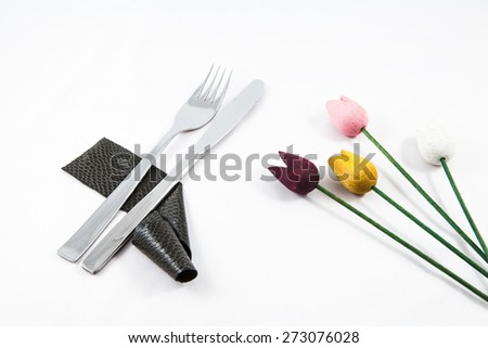 Composition of cutlery on a white background for branches and a decorative starfish and shells for informal dinners or family celebrations - stock photo