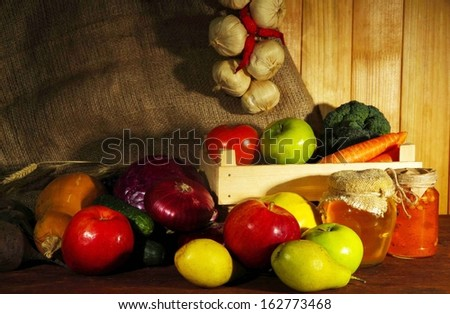 Composition of different fruits and vegetables on table on sackcloth background - stock photo