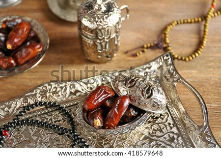 Composition of dried dates in holiday dish and rosary on wooden background - stock photo