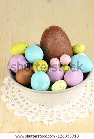 Composition of Easter and chocolate eggs and simnel on wooden table close-up - stock photo