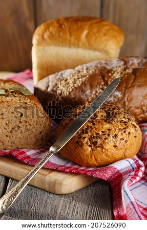 Composition of fresh baked bread, knife and kitchen towel, on wooden background