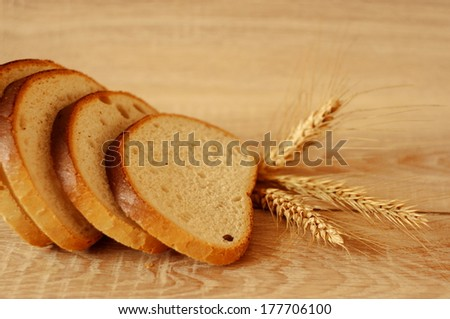 Composition of fresh bread and wheat on the wooden table - stock photo