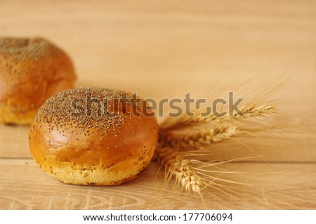 Composition of fresh bread rolls  with poppy seed and wheat on the wooden table - stock photo