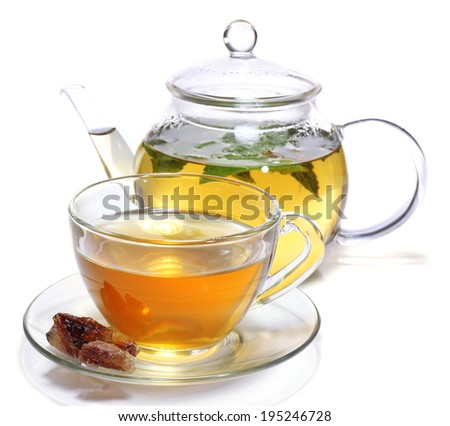 Composition of fresh mint tea in glass cup and teapot and brown sugar isolated on white