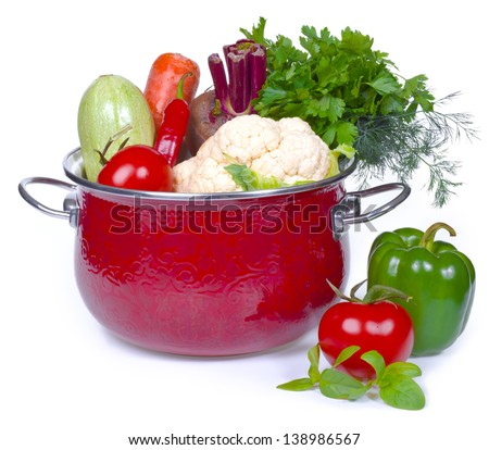 Composition of fresh vegetables in red casserole pot
