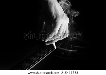 Composition of guitar and man's hand with cigarette smoking on black background - stock photo
