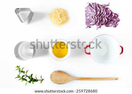 Composition of ingredients and kitchen utensils used for the preparation of red cabbage risotto. Above view over white background, natural light. - stock photo