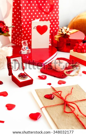 Composition of many Valentine's day festive objects-gift boxes, presents, greeting cards, ribbons and jewellery. Indoors vertical image.