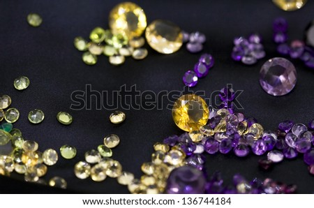 Composition of mixed colorful faceted gemstones on black background - stock photo
