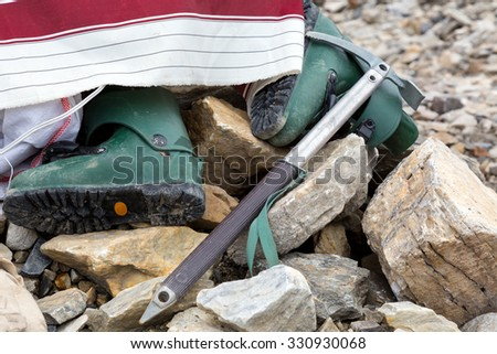 Composition of Mountain Climbing Footwear and Gear in Stones Green Plastic High Altitude Old Boots and Vintage Style Ice Axe - stock photo