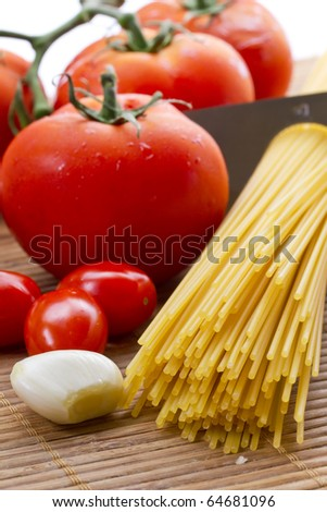 Composition of pasta, tomato and garlic - stock photo