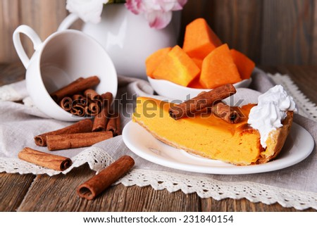 Composition of piece of pumpkin pie on plate, cup and flowers in vase on wooden background - stock photo