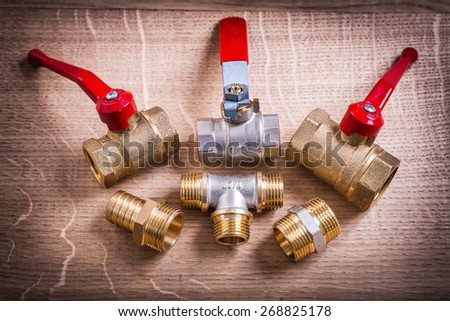 Composition Of Plumbing Tools Brass Pipe Connectors On Wooden Board  - stock photo