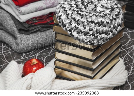 Composition of reading and relaxation at winter trip. Stack of winter clothes with red apple and books with glossy edge. Books wrapped beret and warm scarf. - stock photo